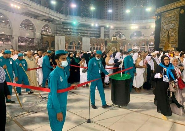 Des travailleurs sanitaires portant des masques protecteurs nettoient le complexe de la Grande Mosquée de La Mecque le 27 février 2020.