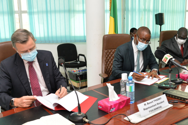 Signature d'une convention de financement du programme conjoint sahel entre Amadou Hott, ministre sénégalais de l'Economie, du Plan et de la Coopération et Benoit Thierry, représentant du Fonds international de développement agricole (Fida)