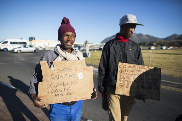 Deux chômeurs vantent des emplois occasionnels dans une rue du Cap. EFE-EPA / Nic Bothma