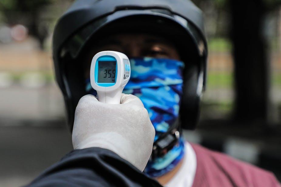 Un gardien de sécurité vérifie la température corporelle d'un motocycliste à titre préventif.