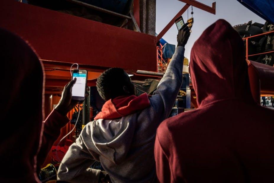 Les migrants essaient d'avoir un réseau sur leurs téléphones à Algésiras, en Espagne. Photo par Ignacio Marin / Agence Anadolu / Getty Images