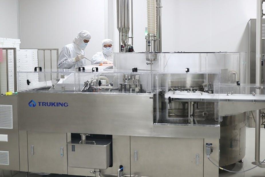 Les membres du personnel travaillent dans une usine de production de vaccins COVID-19 de Sinovac à Pékin. Zhang Yuwei/Xinhua via Getty