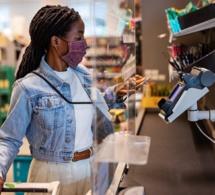 Une femme place son téléphone portable sur un lecteur de carte de crédit à la caisse d'une épicerie. Luis Alvarez via Gettyimages